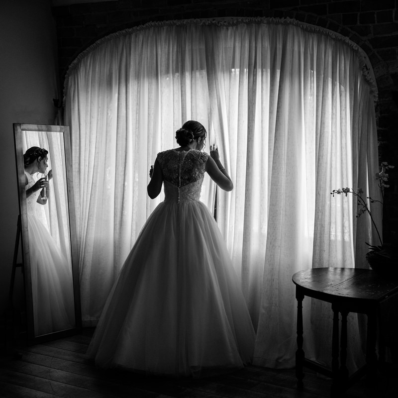 Bride with mirror reflection peering through the curtains to look outside at Dodmoor House