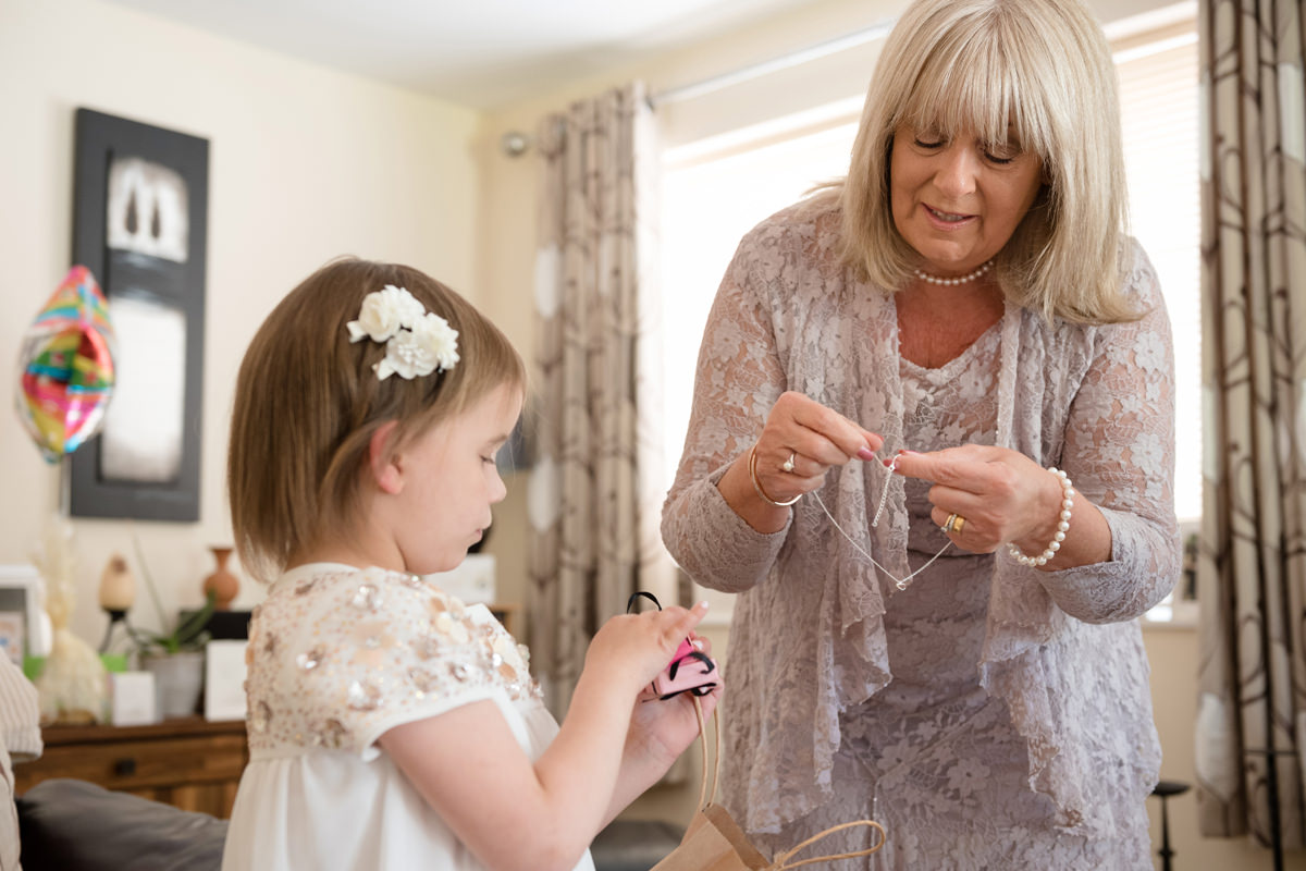 Bride's mum helping her granddaughter with a necklace