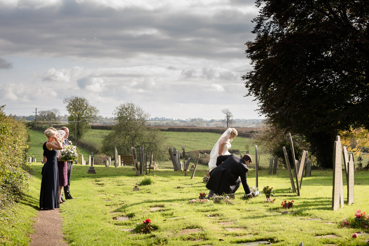 Laying flowers at a grave on a wedding day
