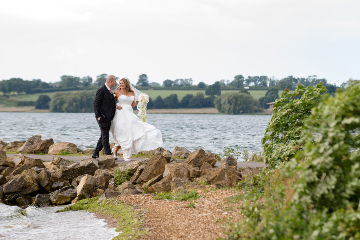 Bride and groom walking arm in arm as they leave Normanton church