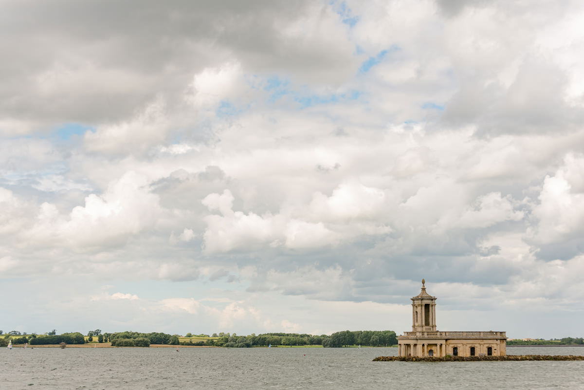 View of Normanton church with a partially cloudy sky and tiny bit of blue sky