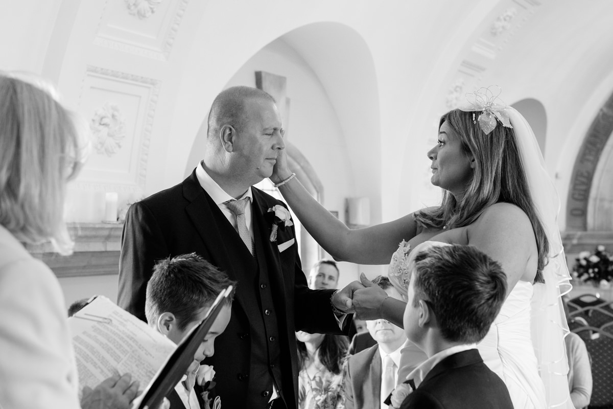 Bride stroking groom's face during ceremony at Normanton Church