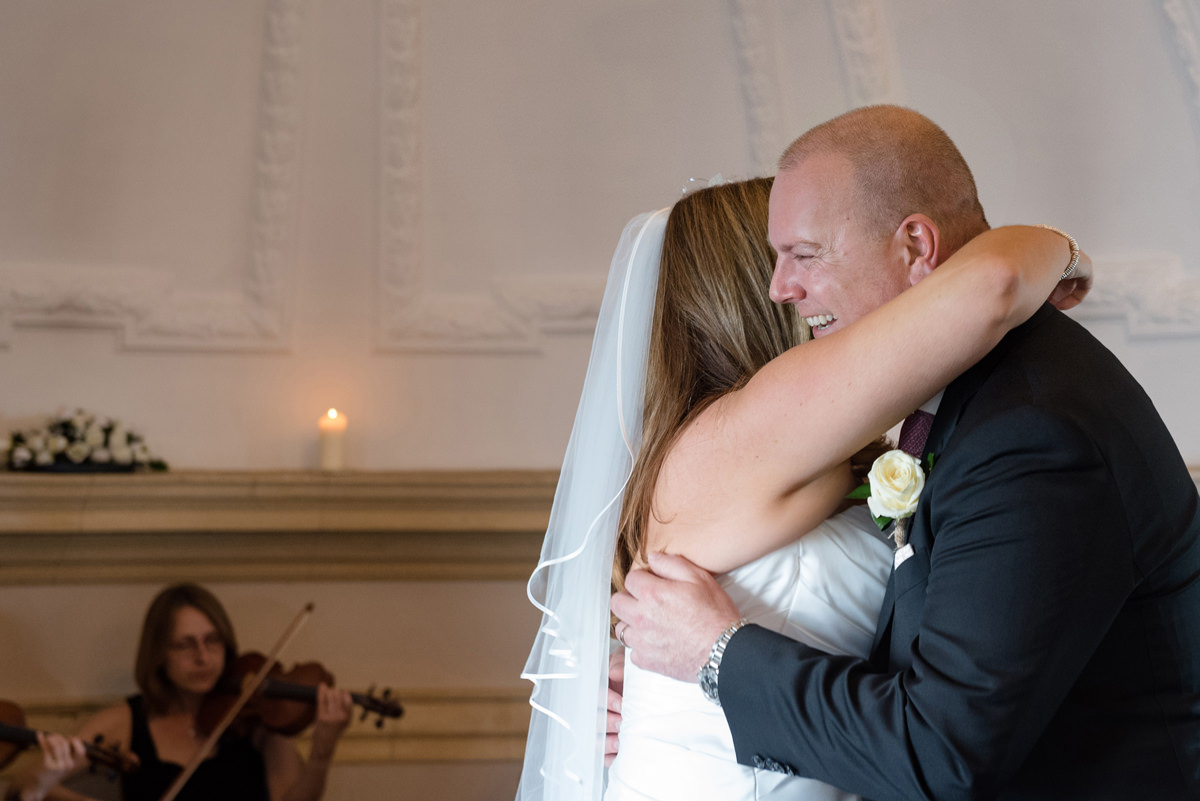 Bride and groom hugging after getting married at Normanton Church