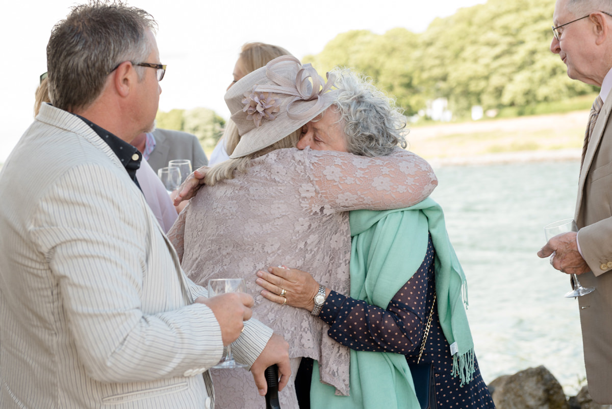 Wedding guest hugging mother of the bride at Normanton Church
