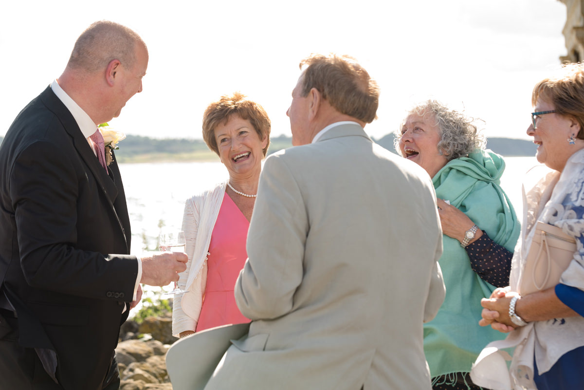 Wedding guests laughing with the groom at Normanton Church