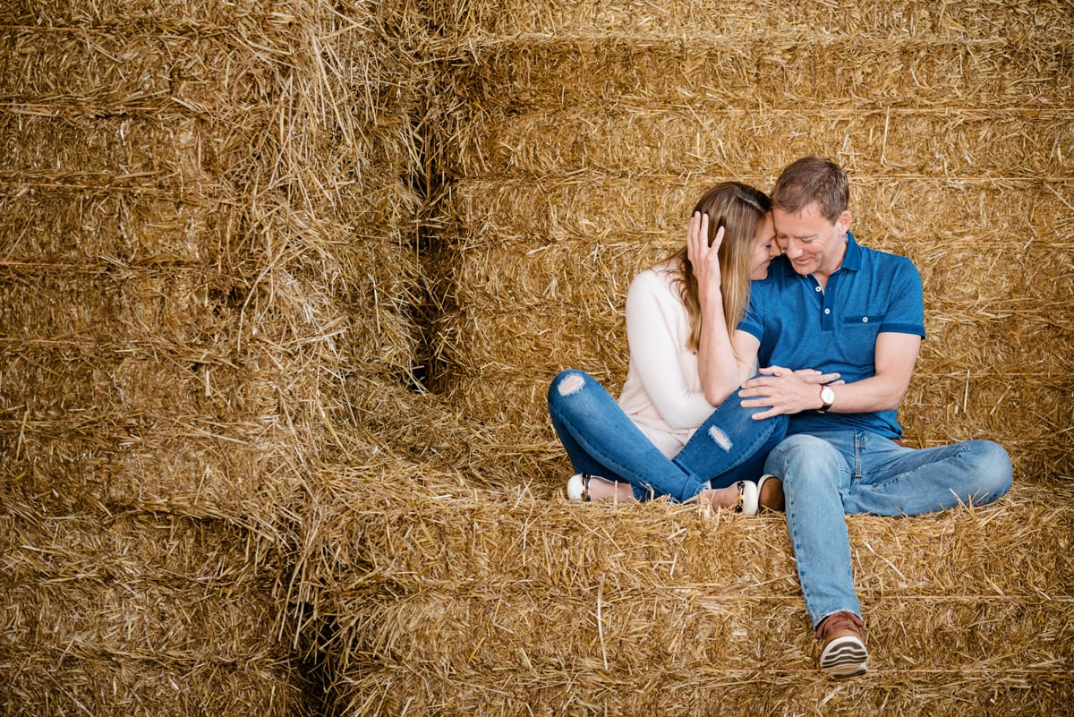 Engaged couple snuggling up on a hay bale