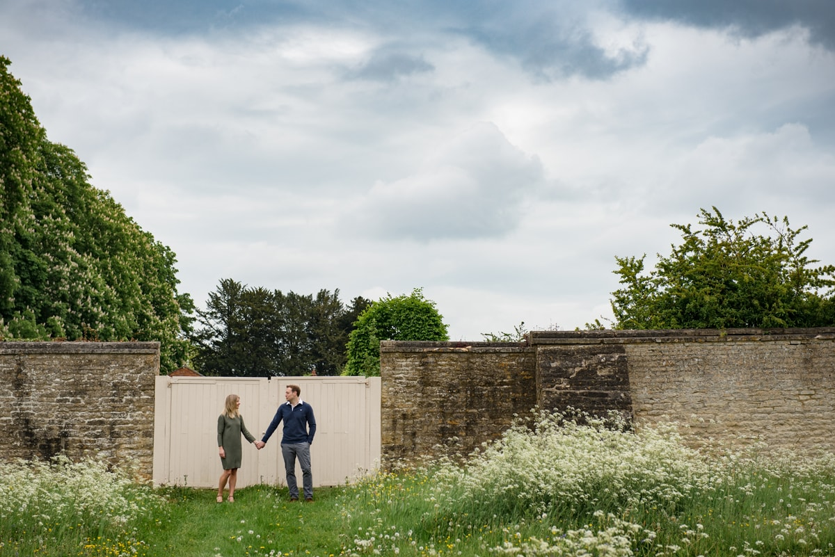 Engaged couple in front of garden gates with big cloudy sky