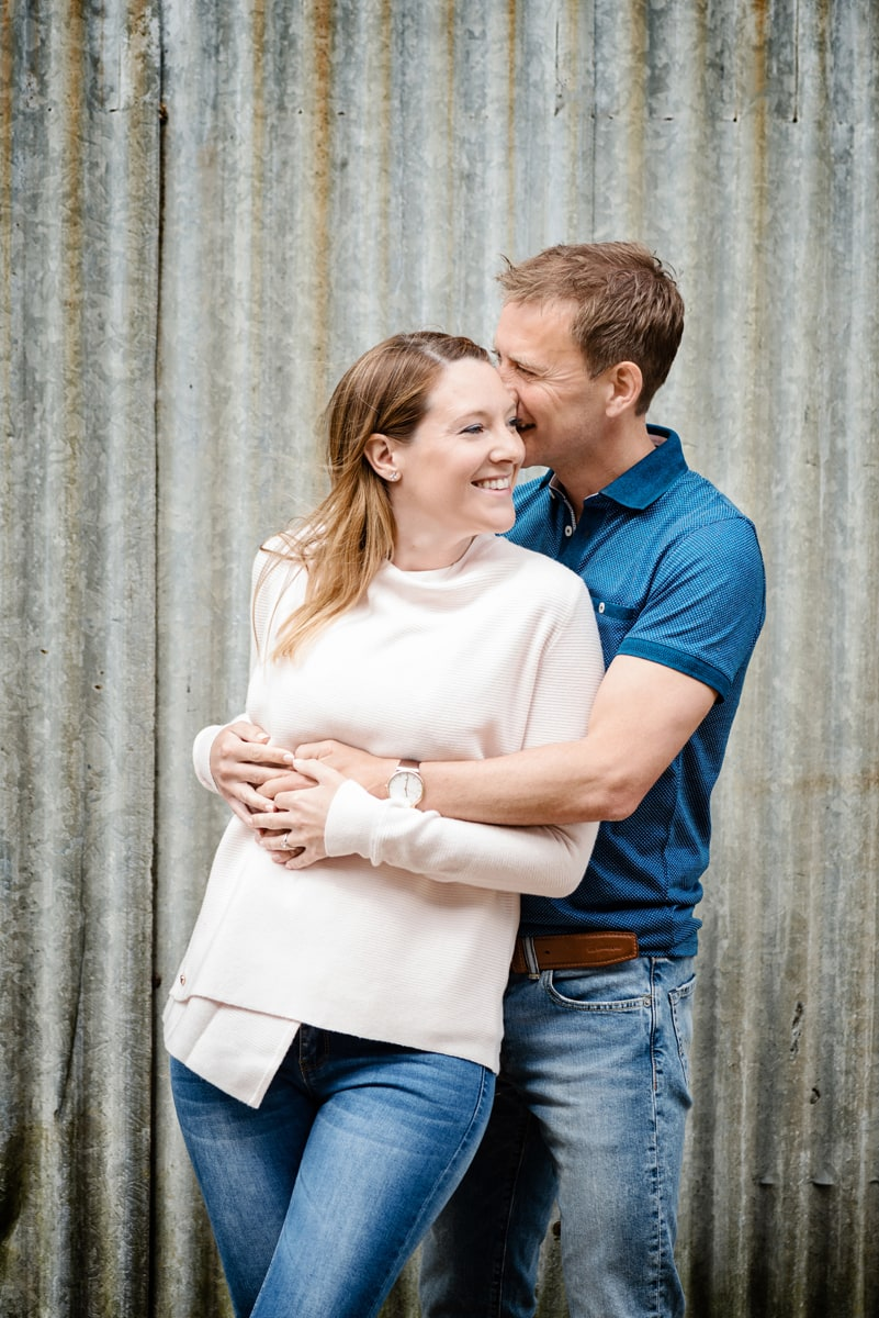 Engaged couple cuddling in front of silver barn door