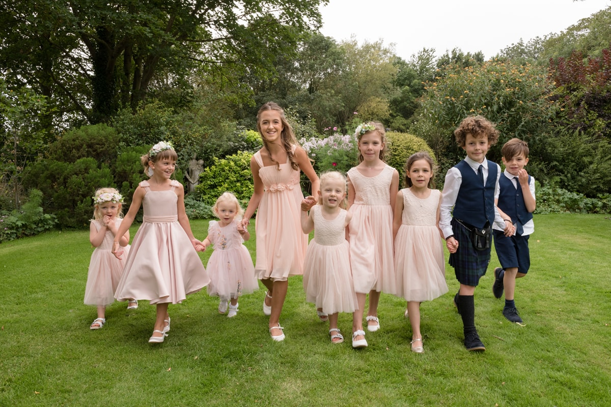Bridesmaids and page boys holding hands and walking