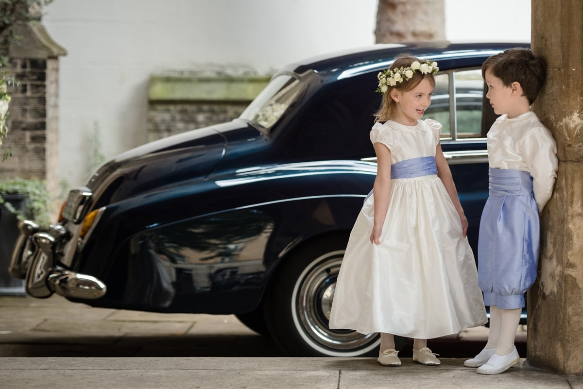 Page boy and flower girl chatting in front of vintage wedding car
