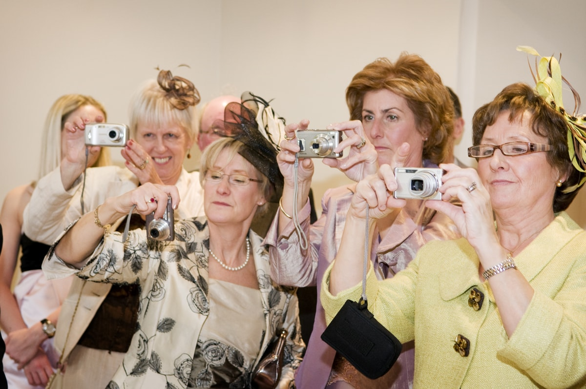 A line of wedding guests in hats taking photos