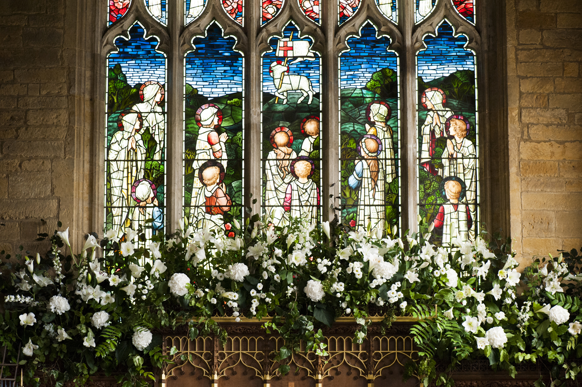 White wedding flowers on altar at Great Brington church