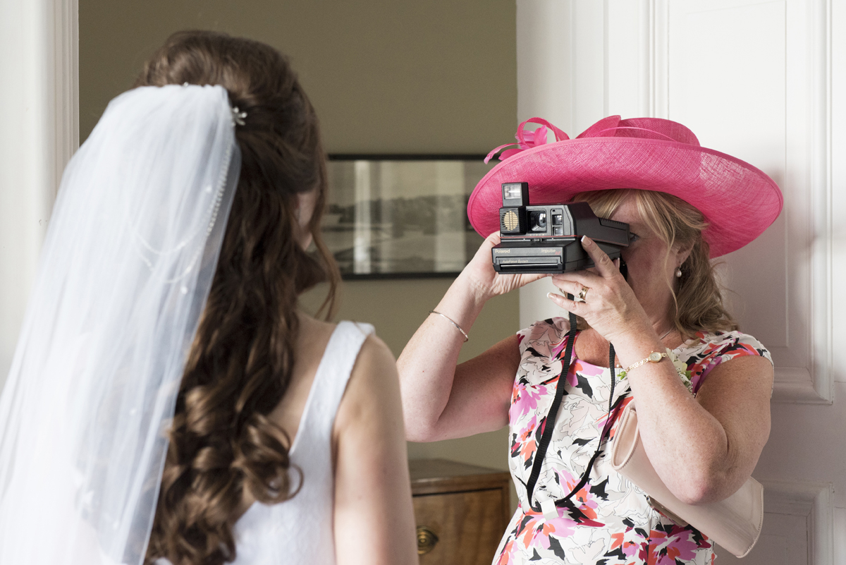 Mother of bride taking photo of bride