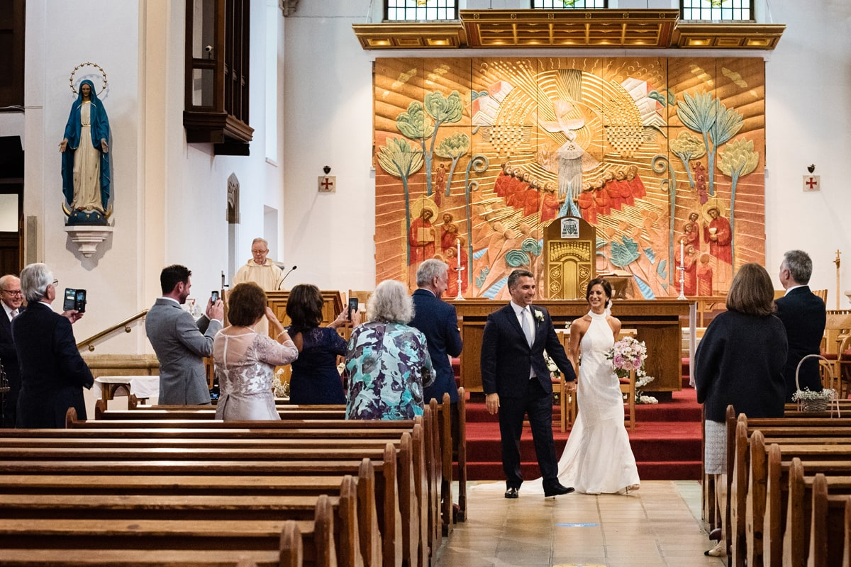 Couple walking down aisle after intimate wedding at Northampton Cathedral