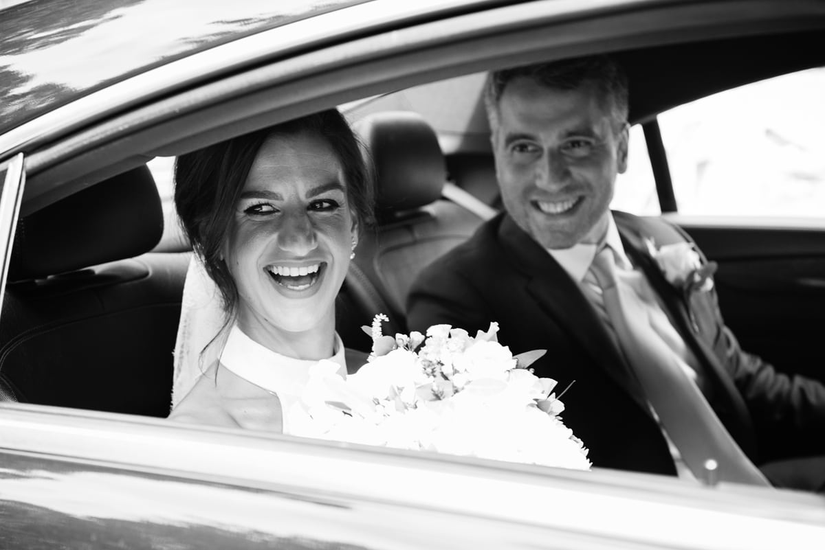 Bride laughing and looking out of car window