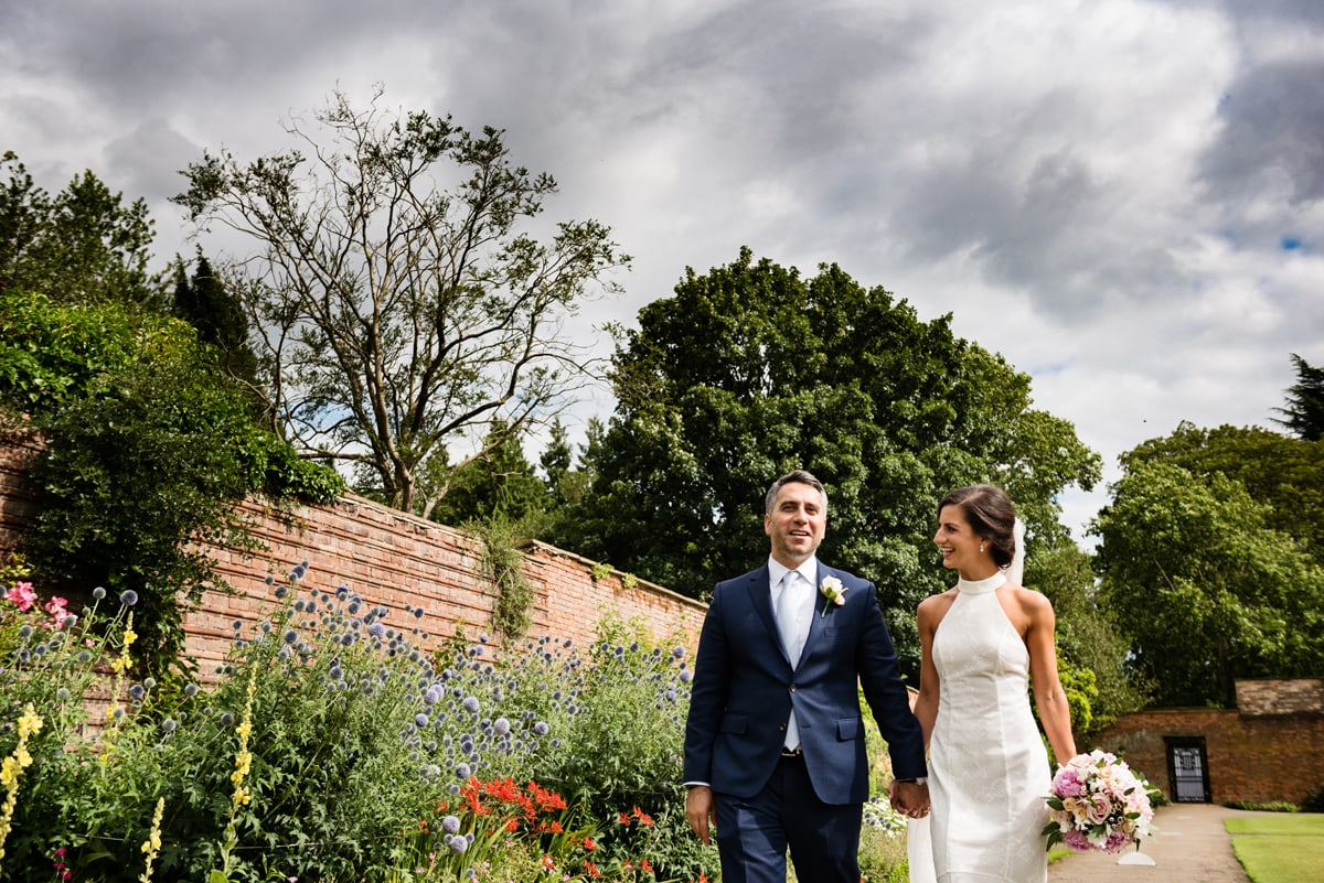 Newlyweds walking through the walled garden at Delapre