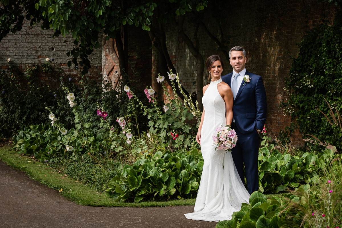 Wedding photo by foxgloves in walled garden at Delapre Abbey