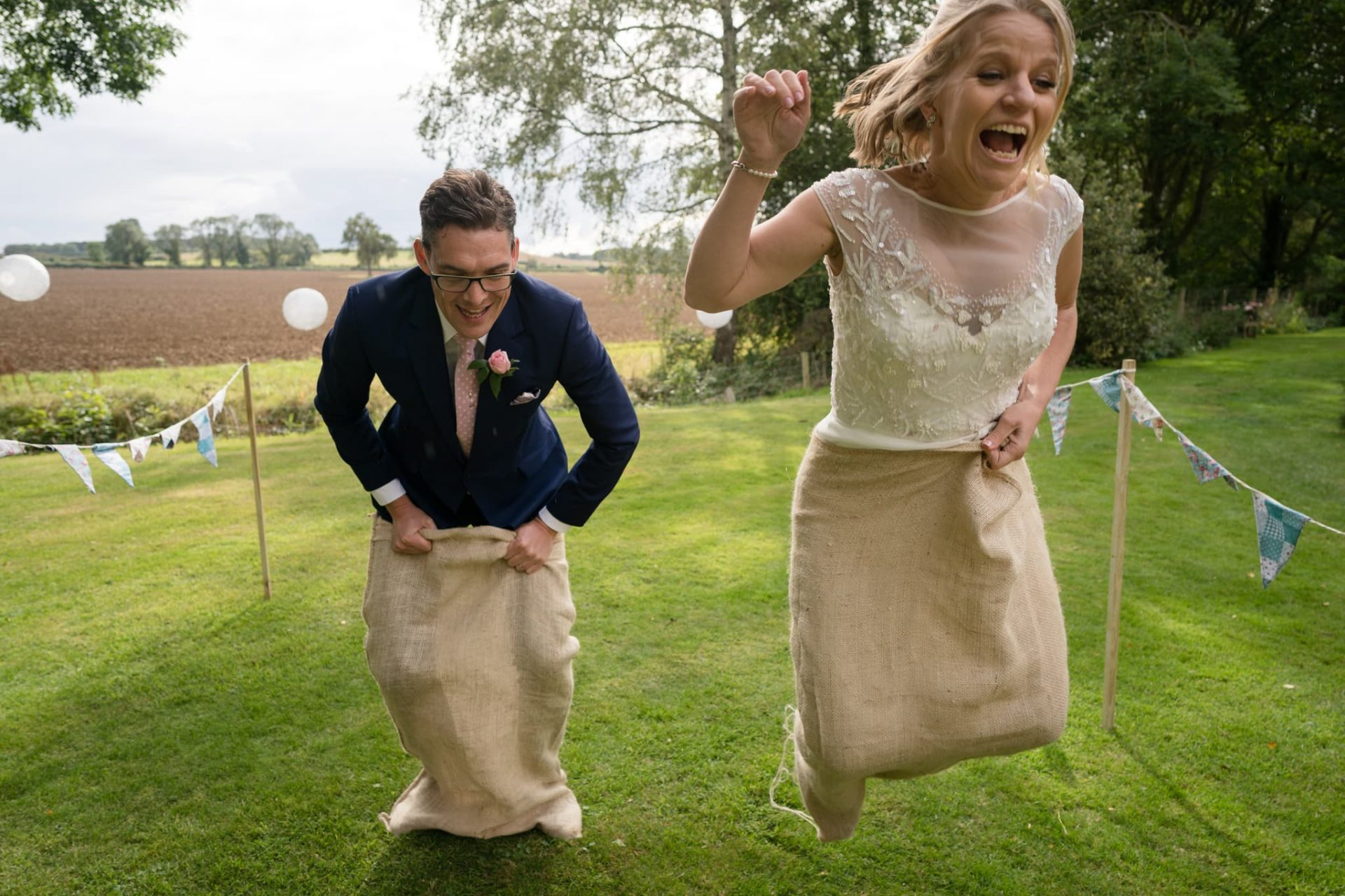 Bride and groom competing in a sack race