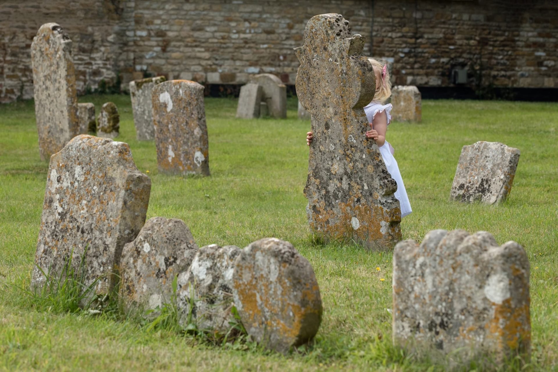 Little girl playing hide and seek amongst gravestones