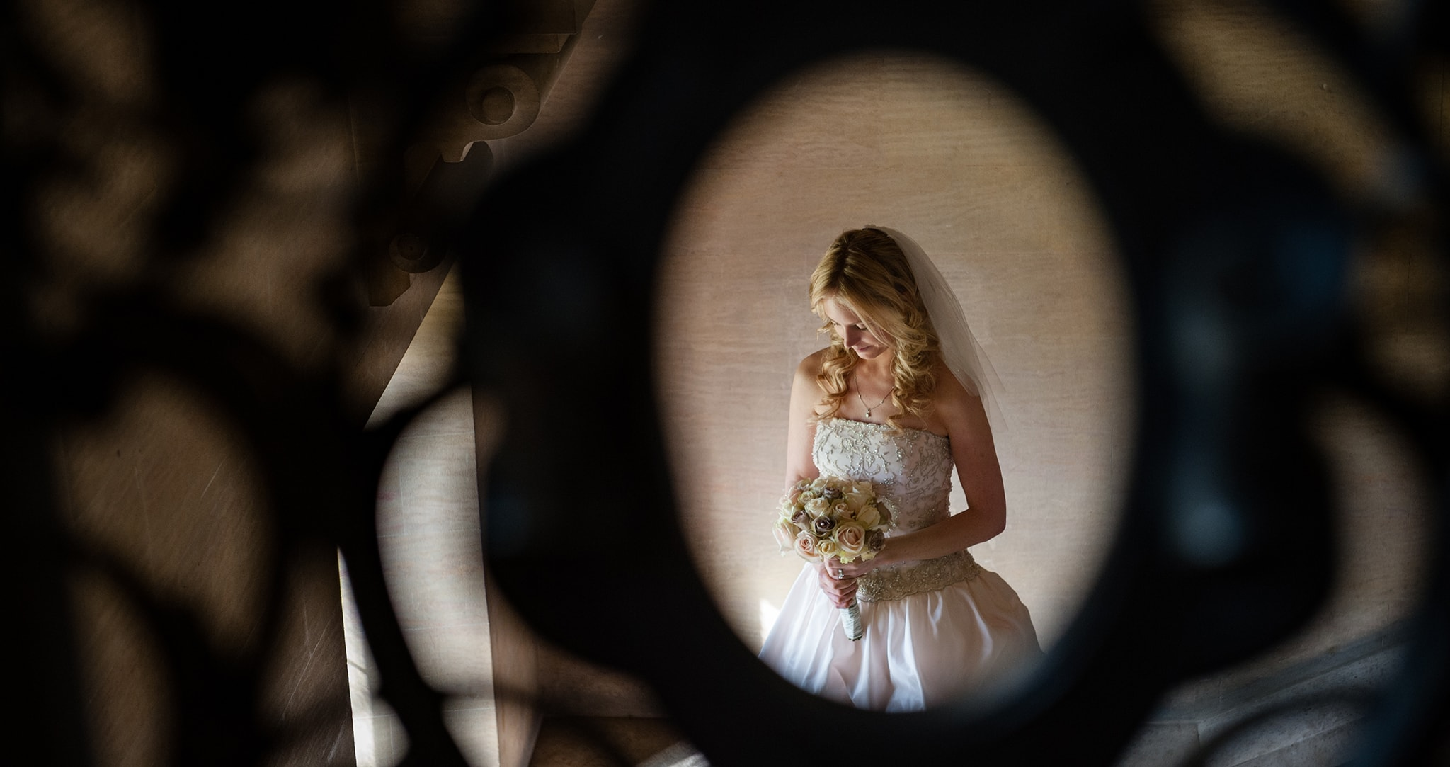 Bride through stair balustrade at Harlaxton Manor