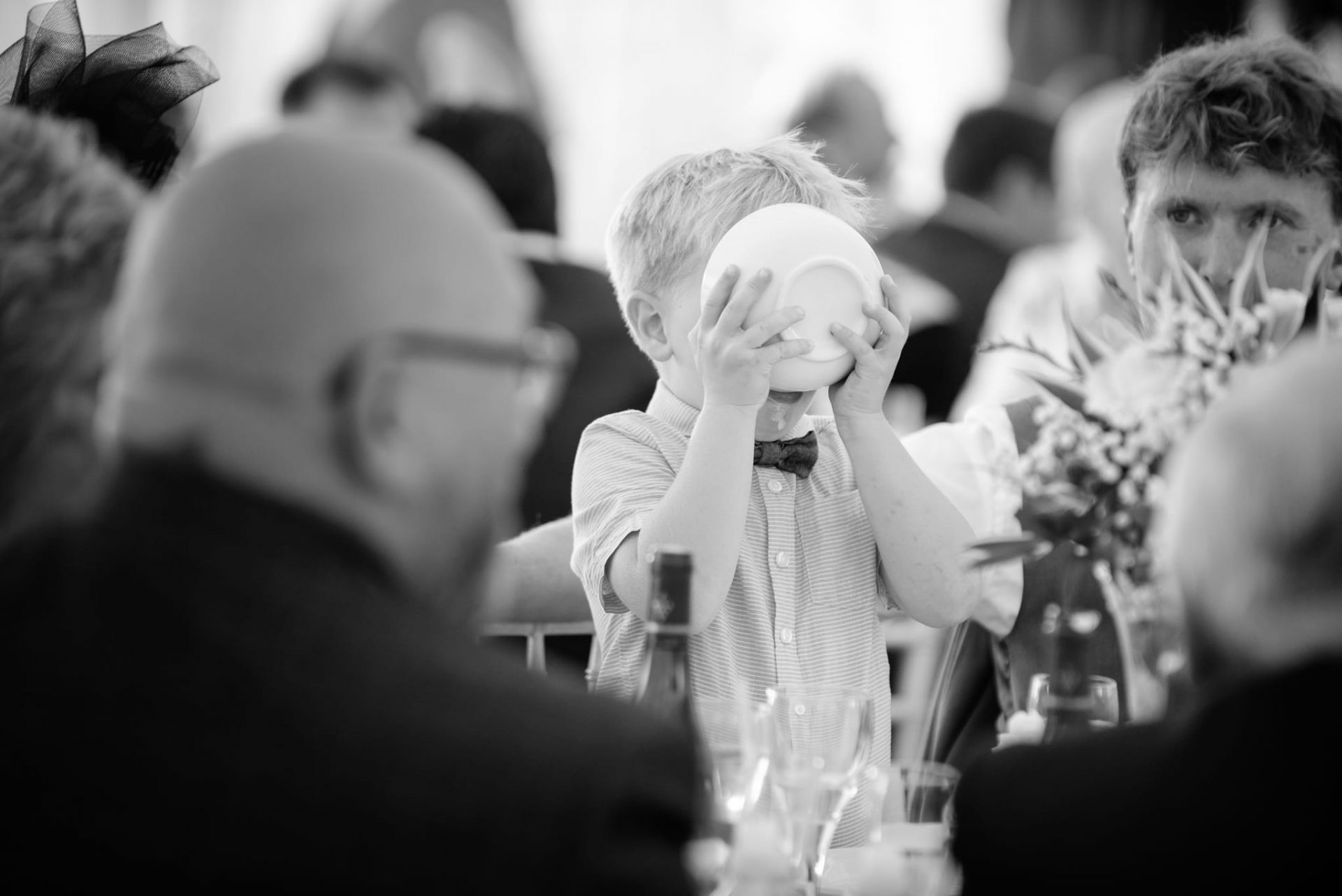 Young wedding guest drinking cream from bowl