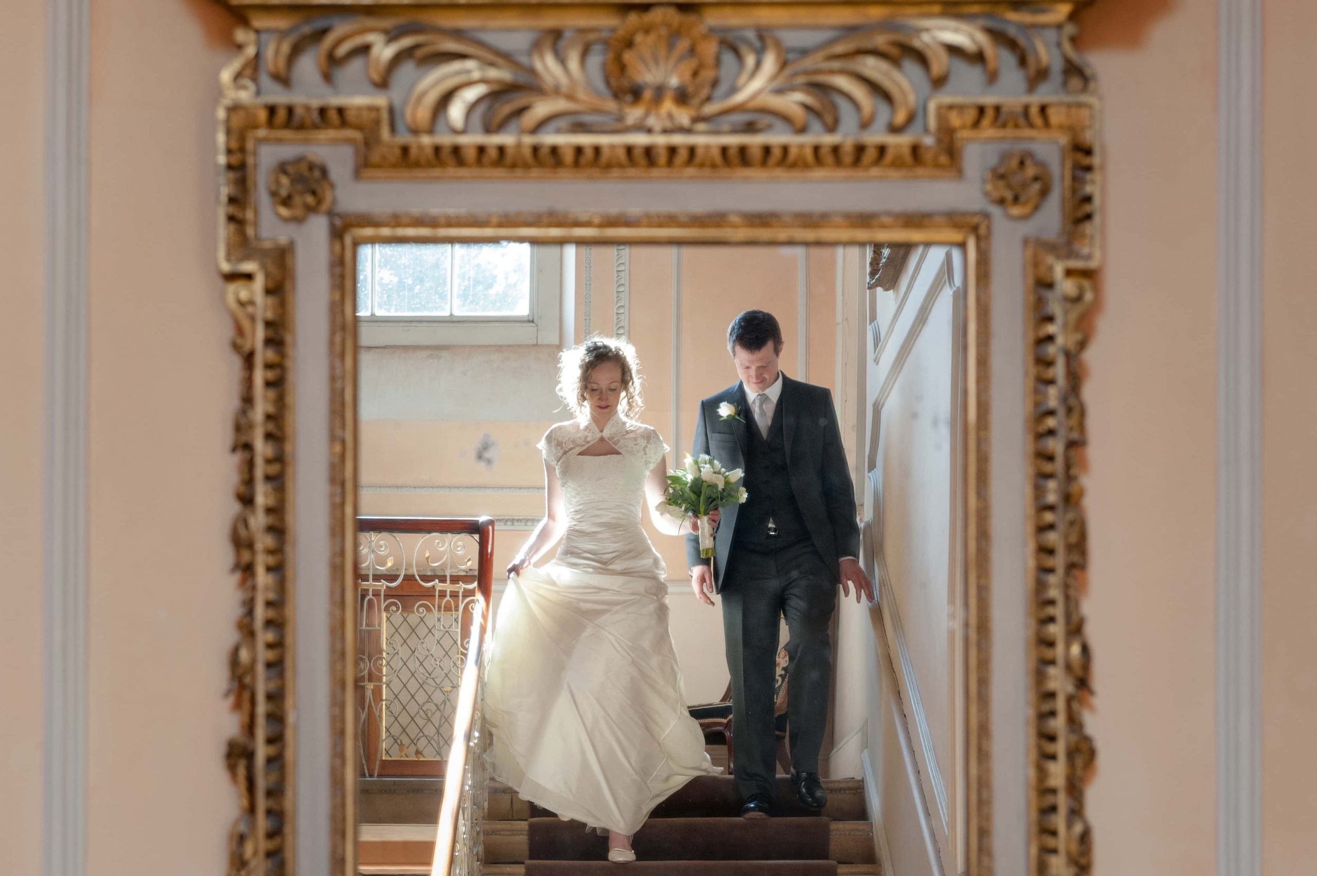 Bride and groom coming down the staircase at Kelmarsh Hall