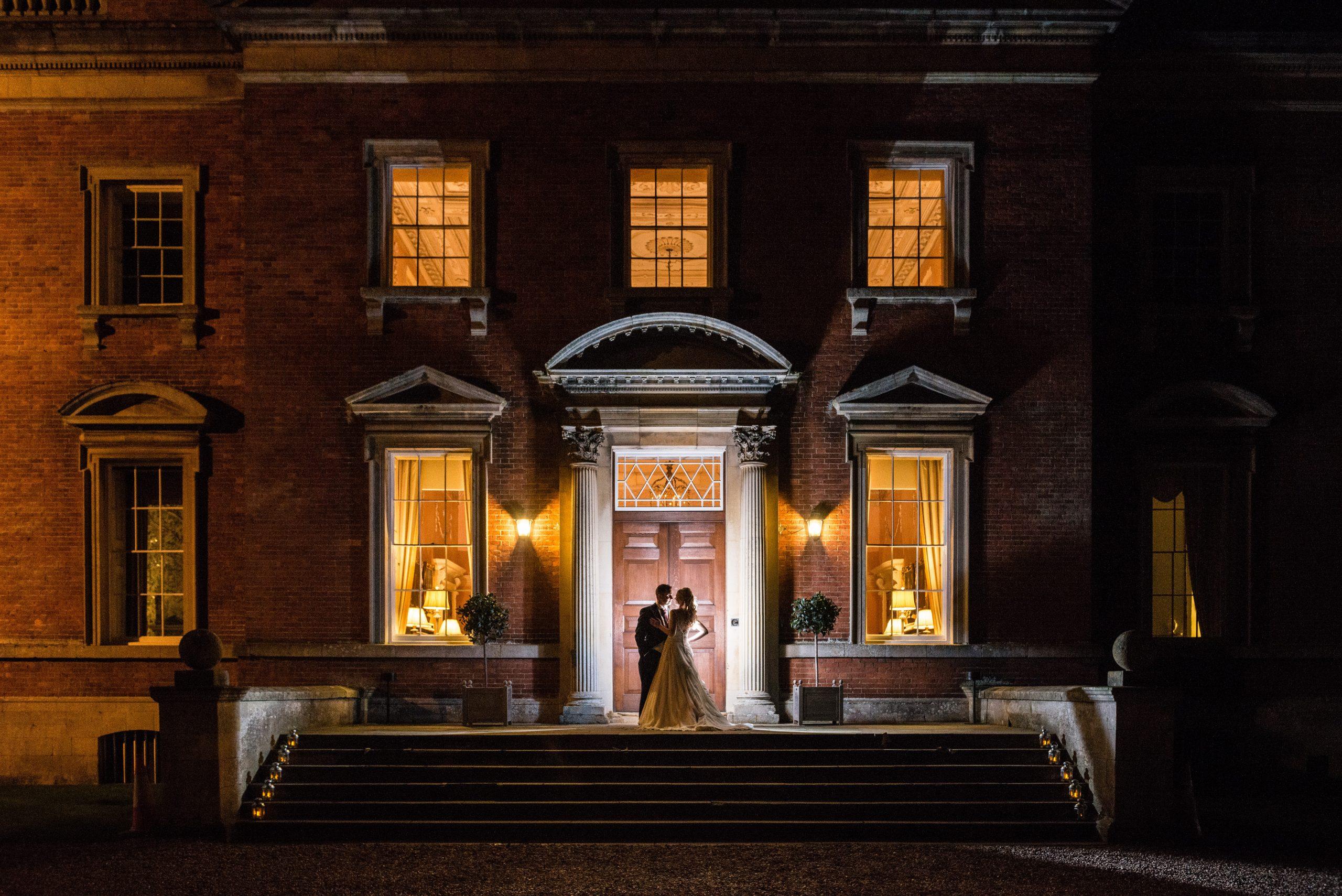 Bride & groom on the front steps of Kelmarsh Hall at night