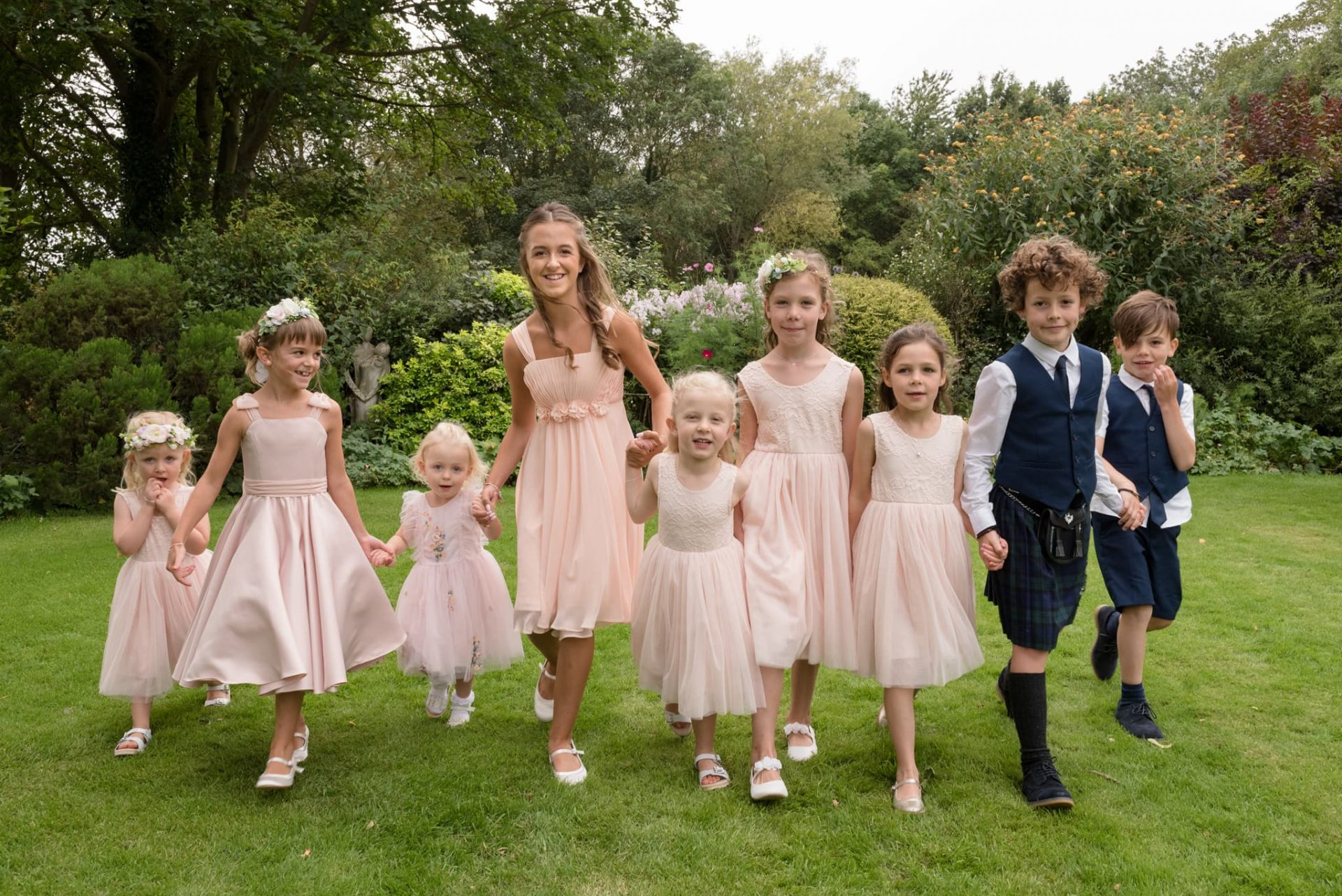Flower girls and page boys walking hand in hand for a group photo