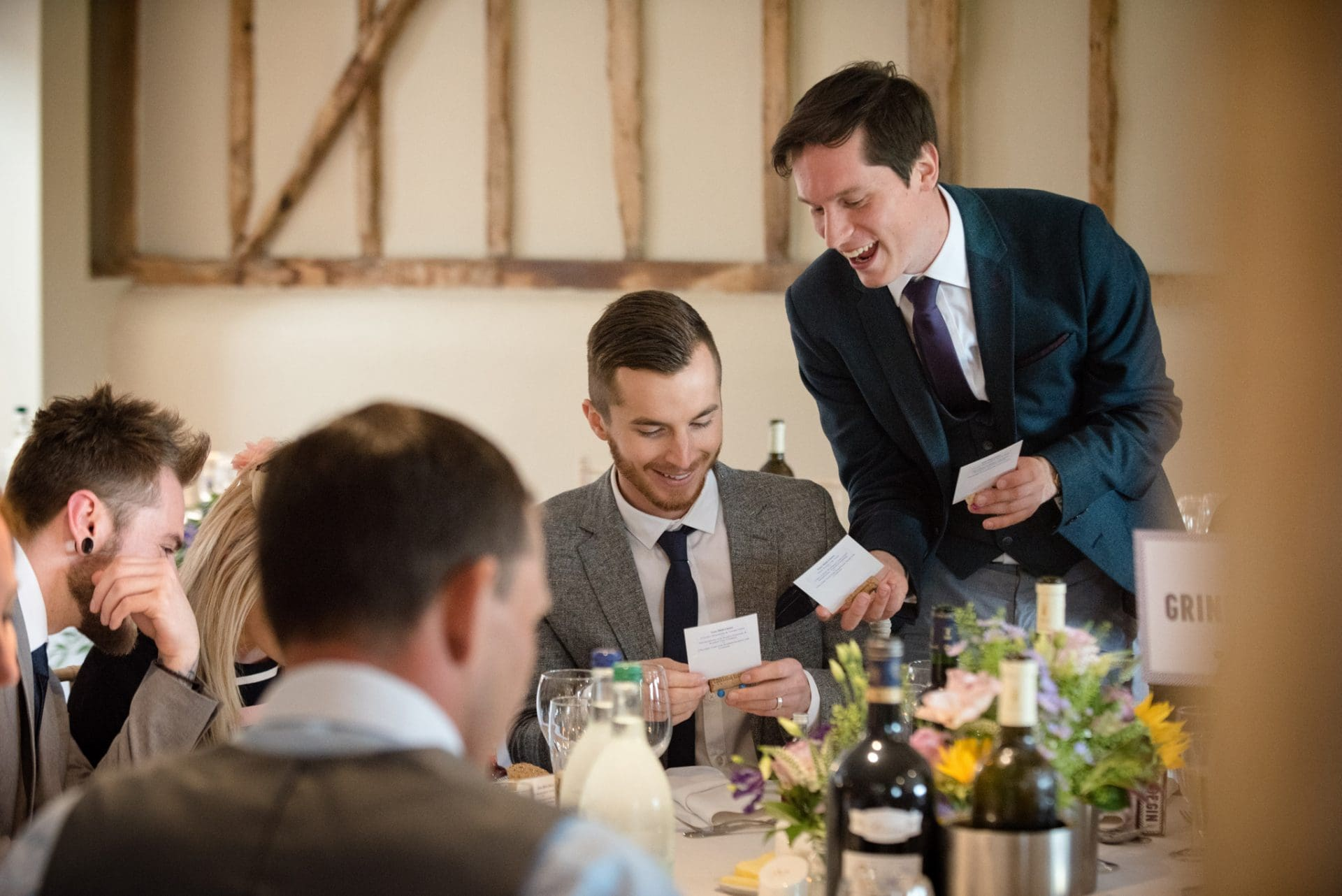 Wedding guests laughing at polaroid placenames